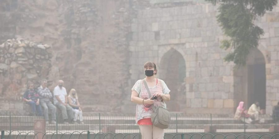 Tourists wears an anti-pollution mask amid heavy smog as the air quality further dips to severe category, at Qutub minar in New Delhi