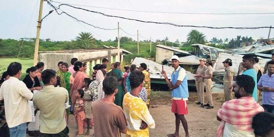 People outside the dry fish unit that was demolished in Gopalpur