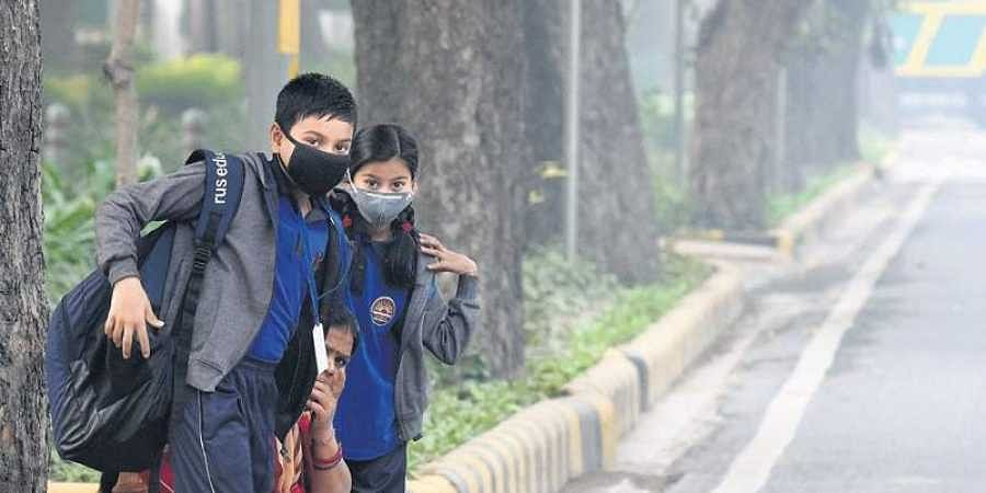 Students cover their faces with masks to protect themselves from morning air pollution, at Firoz Shah Road.