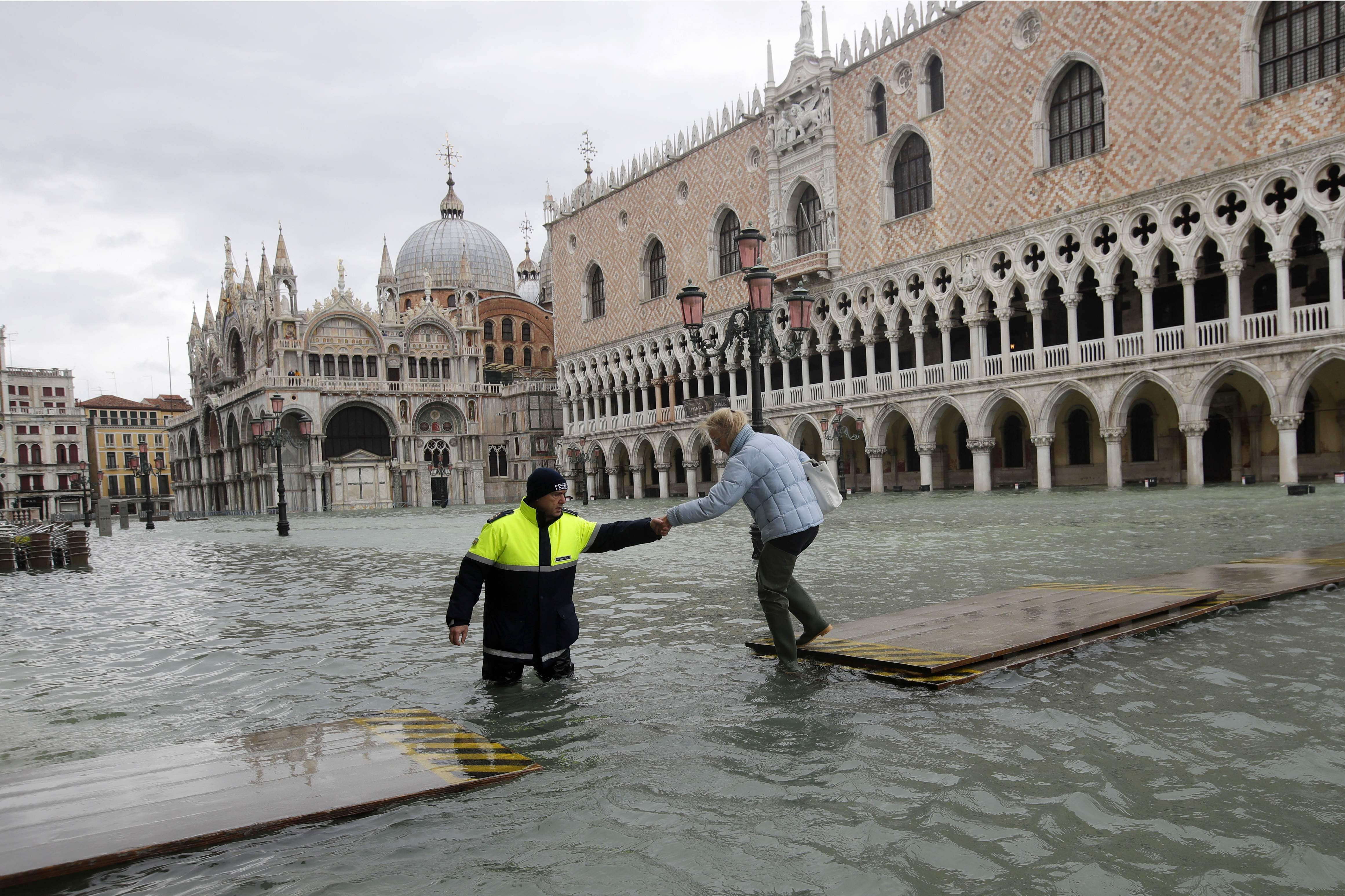 A city worker helps a woman who decided to cross St. Mark square on a gangway, in spite of prohibition, in Venice, Italy, Sunday, Nov. 17, 2019.
