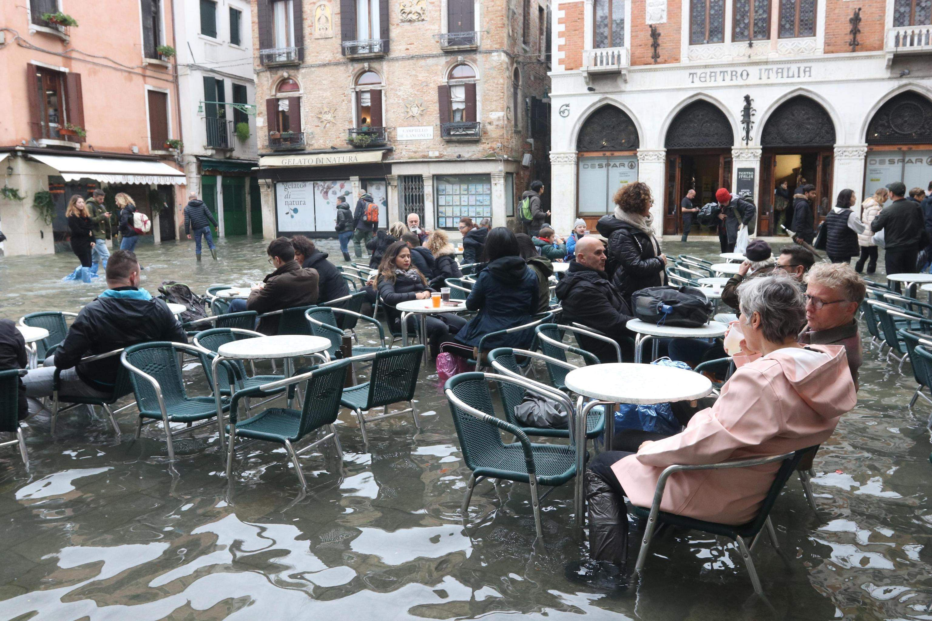 Life goes on: Tourists and residents resume their normal routine at a bar in Venice, Italy, Sunday, Nov. 17, 2019. High tidal waters returned to Venice on Sunday, days after the city experienced its worst flooding in more than 50 years.
