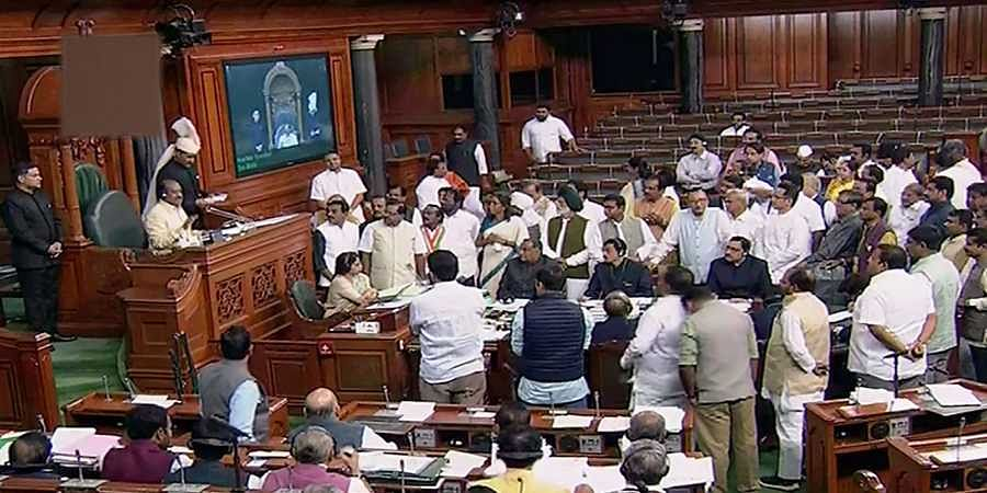 Opposition members protest in the Lok Sabha during the Winter Session of Parliament in New Delhi Tuesday