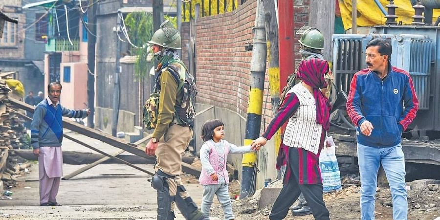 A security person patrols a street in downtown Srinagar on Friday. Though the public transport remained off the roads, private vehicles were seen plying despite security restrictions in the Kashmir Valley