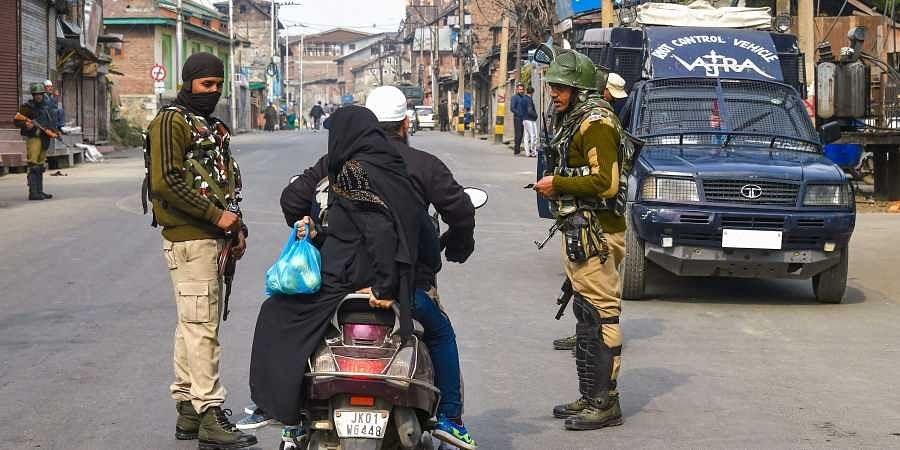 Security personnel ask a scooterist to divert his route during restrictions in parts of Downtown in Srinagar