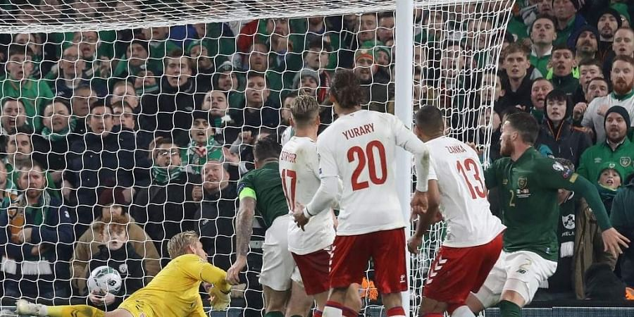 Republic of Ireland's defender Matt Doherty (R) watches his header beat Denmark's goalkeeper Kasper Schmeichel (L) for their first goal during the Group D Euro 2020 football qualification match. (Photo   AFP)