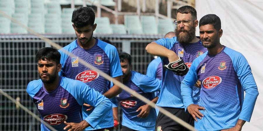 Bangladesh's spin coach Daniel Vettori, second right, and bowler Mahmudullah, right, watch as others practice bowling in the nets ahead of their second cricket Test match against India, in Kolkata.