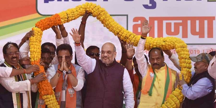 Union Home Minister Amit Shah flanked by Jharkhand Chief Minister Raghubar Das (R) and BJP candidate from Lohardaga Assembly Sukhdeo Bhagat being garlanded by party supporters during an election campaign ahead of Jharkhand Assembly Elections, in Lohardaga
