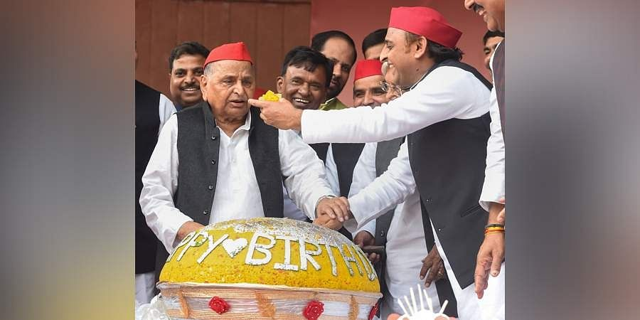 Samajwadi Party founder Mulayam Singh Yadav being offered sweets by his son and party President Akhilesh Yadav during his 81st birthday celebrations, at party office in Lucknow