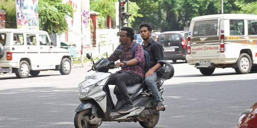 Two men travel on a two-wheeler without wearing helmets.