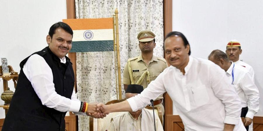 Newly sworn in Chief Minister of Maharashtra Devendra Fadnavis shakes hands with his Deputy Chief Minister Ajit Pawar in Mumbai Saturday Nov. 23 2019.(Photo | PTI)