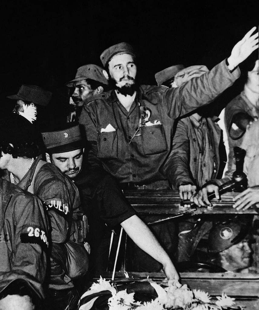 The Cuban rebel leader Fidel Castro, surrounded by the members of his leftist guerrilla movement '26th of July Movement', waves from a jeep 04 January 1959, entering Cienfuegos after the victory over the forces of Cuban dictator Fulgencio Batista.