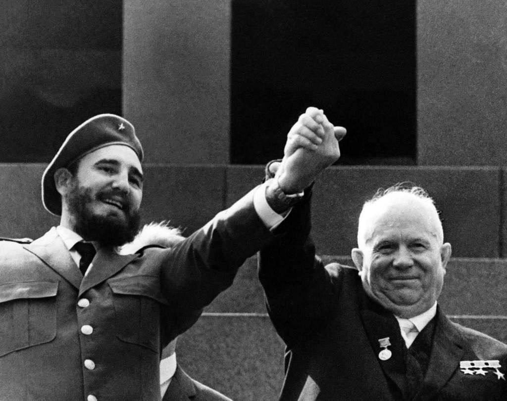 Fidel Castro, Cuban communist revolutionary and Prime Minister of Cuba and Nikita Khrushchev, President of the Council of the Soviet Union clasping hands raises in sign of victory on the stand at the Lenin's Mausoleum on May 01, 1963 in Moscow, USSR.
