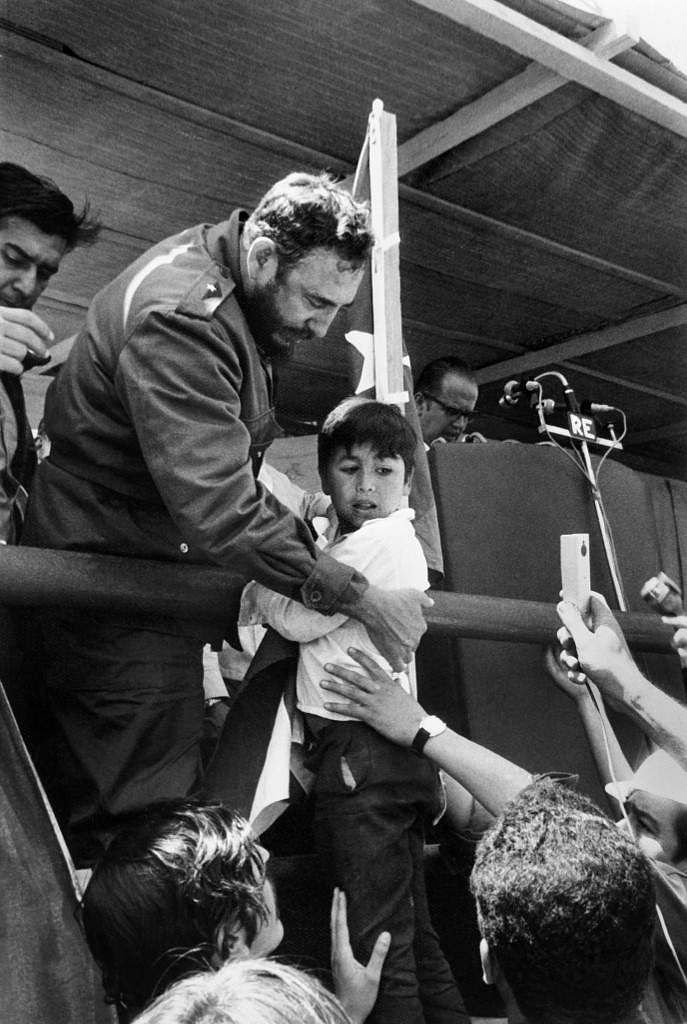 Cuban leader Fidel Castro interrupts his speech to help a child to climb onto the tribune, eluding the security guards, 20 November 1971. Castro is on a ten-day official visit in Chile.