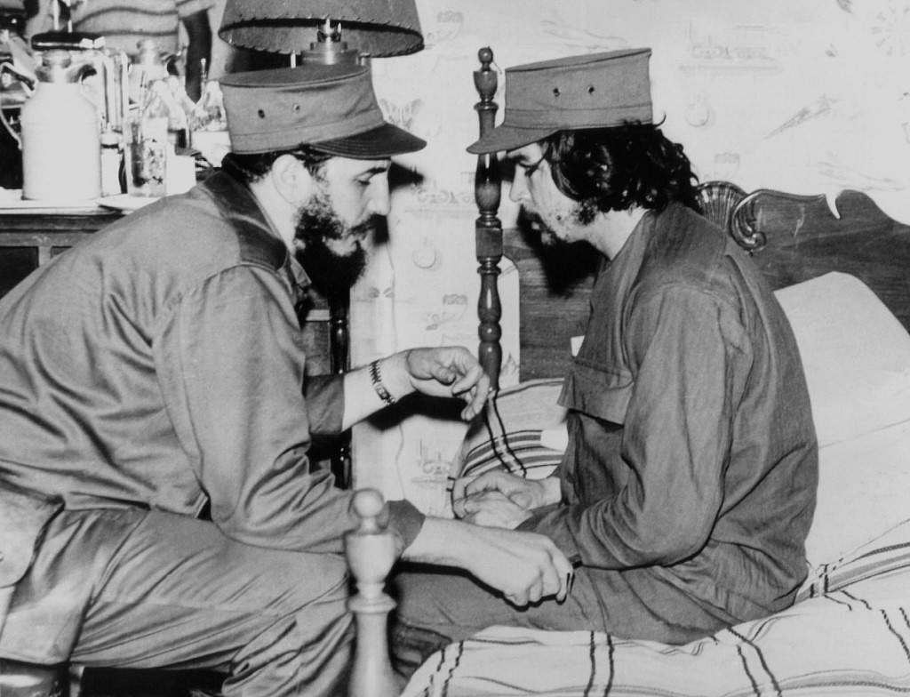 This 1959 file photo shows Cuban Fidel Castro (L), then 33 years old, chatting with ailing 31-year-old Ernesto Che Guevara, at his barracks in Havana, shortly after both led the revolution that overthrew the Batista regime.