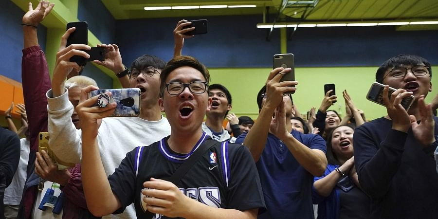 Supporters of pro-democracy candidate Angus Wong celebrate after he won in district council elections in Hong Kong, early Monday, Nov. 25, 2019. Vote counting was underway in Hong Kong early Monday after a massive turnout in district council elections seen as a barometer of public support for pro-democracy protests that have rocked the semi-autonomous Chinese territory for more than five months.