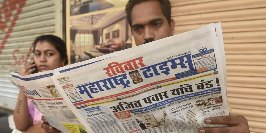 A local reads newspaper fronted with headlines on Maharashtra government formation in Mumbai Sunday Nov. 24 2019. (Photo | PTI)