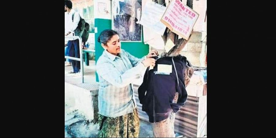 A woman picks up one of the jackets put up by the residents of RR Nagar, on Tuesday.
