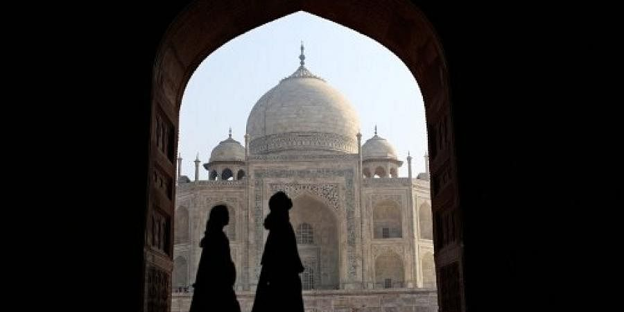 Indian tourists walk past an archway at the historic Taj Mahal in Agra.