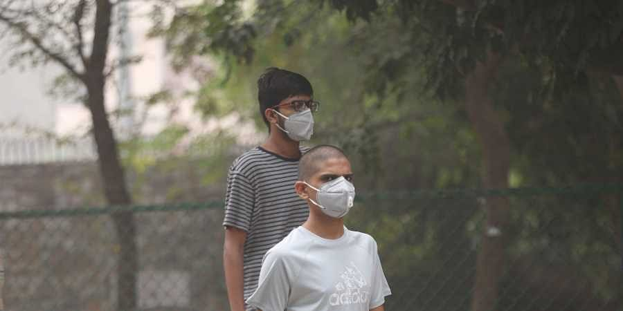 People wear masks during their morning walk in a park amid heavy smog in New Delhi.