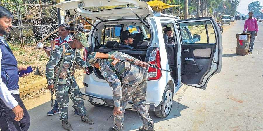 Security forces check a four-wheeler ahead of the first phase of Jharkhand Assembly Election, at NH 75.