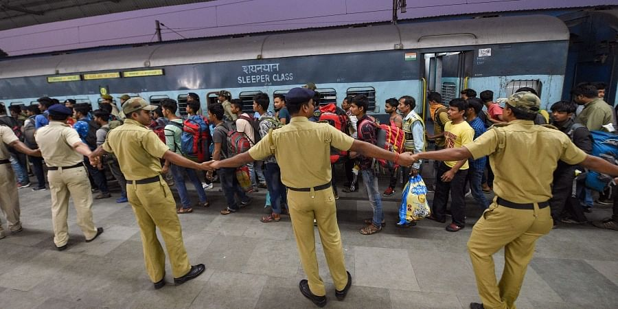 Security personnel form a human chain as workers arrive at the station from Jammu and Kashmir in Kolkata Monday Nov. 4 2019. | (Photo | PTI)