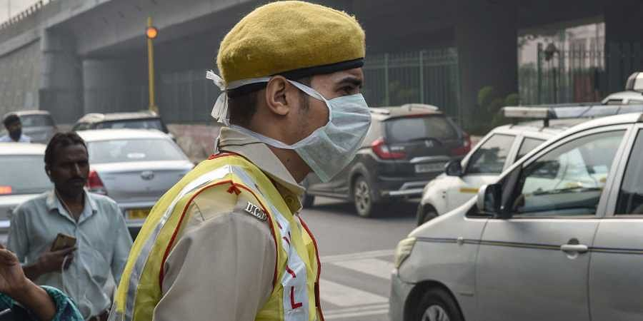 A Civil Defence volunteer wearing a pollution mask on duty to help implement the odd-even scheme in New Delhi Monday Nov. 4 2019. | (Photo | PTI)