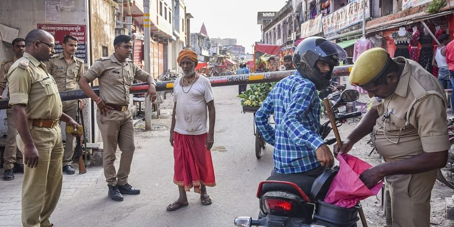 Police personnel checks a rider as other stand guard in Ayodhya.