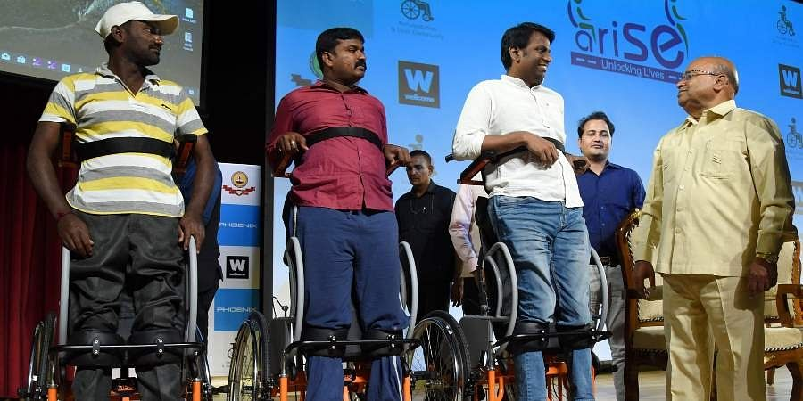 Union Minister Thaawarchand Gehlot with differently abled persons on the 'Standing Wheelchair'.