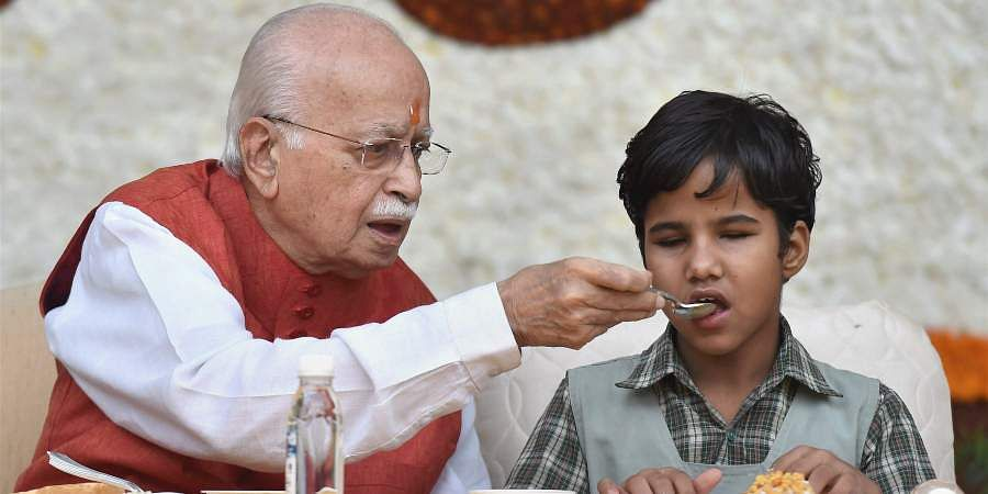 Senior BJP leader LK Advani offering food to a blind student as he celebrates his 90th birthday in New Delhi.