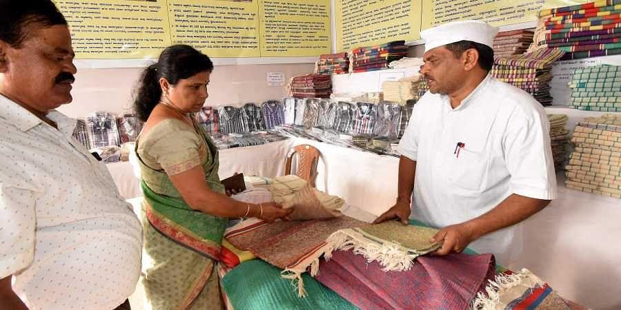 Nanjundaswamy interacting with customers at the Dasara stall in Mysuru by Prisons department. (Photo | Udayshankar S, EPS)