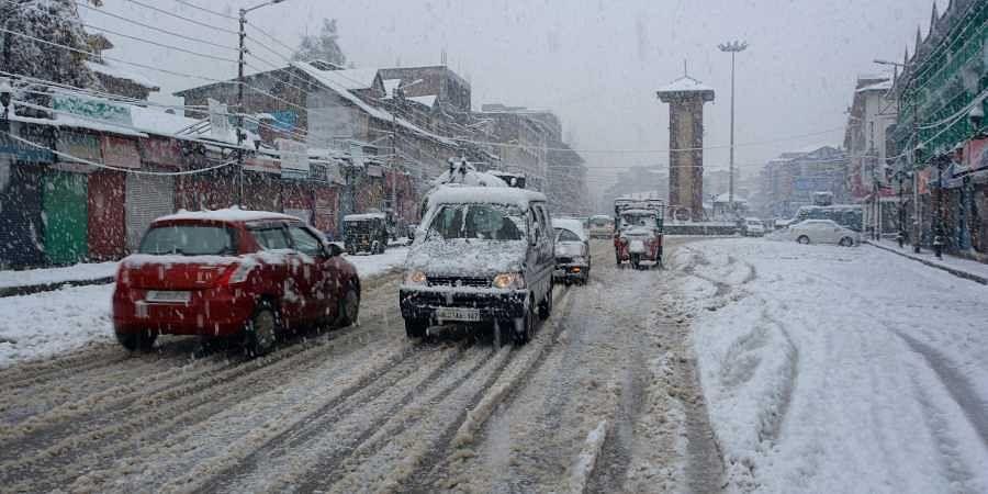 Vehicles move slowly on a snow covered road during season's first heavy snowfall in Srinagar Thursday Nov. 7 2019. | (Photo | PTI)