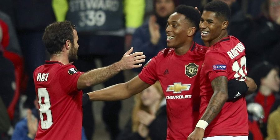Manchester United's Anthony Martial, center, celebrates with Juan Mata and Marcus Rashford, right, after scoring his side's second goal.