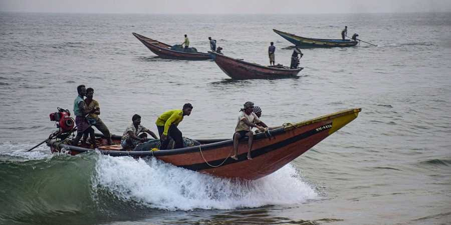 Fishermen take their boats to a safe harbour from the sea following Cyclone Bulbul warning in Puri
