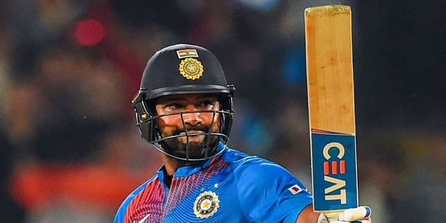India's stand-in captain Rohit Sharma raises his bat after scoring 50 runs during the second T20 cricket match against Bangladesh at Saurashtra Cricket Association Stadium in Rajkot.