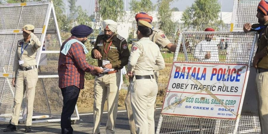 A Sikh pilgrim shows his documents to police before crossing over to Pakistan for the inauguration ceremony of the Kartarpur Corridor in Dera Baba Nanak on November 9, 2019, as Indian Sikh pilgrims visited the shrine of Baba Guru Nanak Dev at the Gurdwara Darbar Sahib.