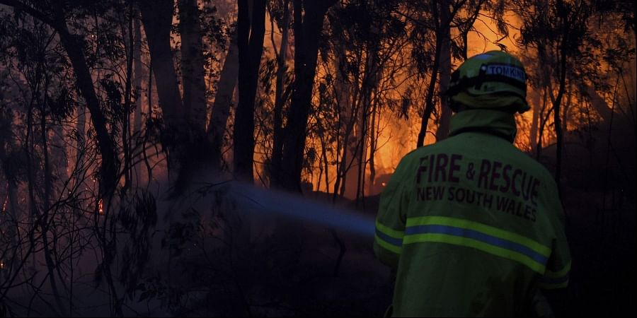 Fire and Rescue NSW firefighters conduct property protection as a bushfire burns close to homes on Railway Parade in Woodford NSW, Friday, Nov. 8, 2019.