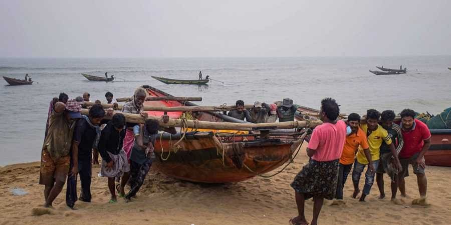 Fishermen pull their boats to away from the sea following Cyclone Bulbul warning in Puri Friday Nov. 8 2019. | (Photo | PTI)