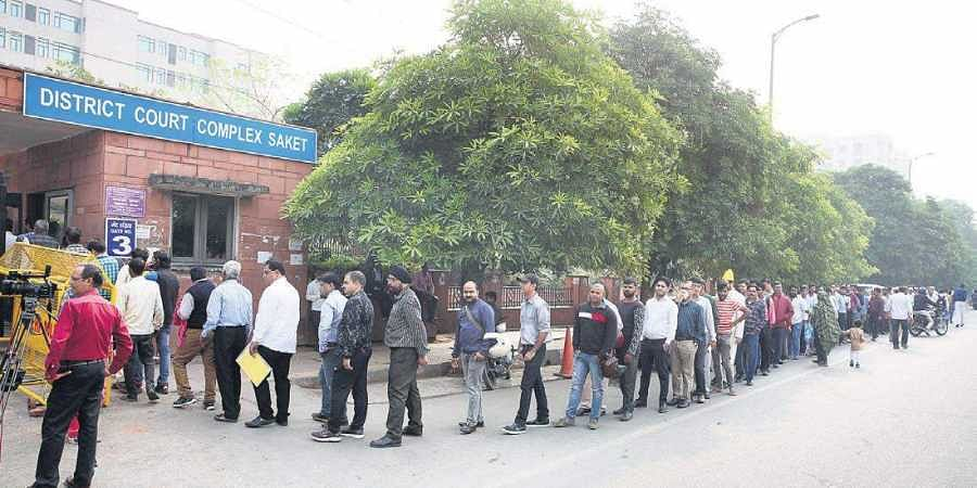 Litigants stand in a queue outside the Saket court in New Delhi.