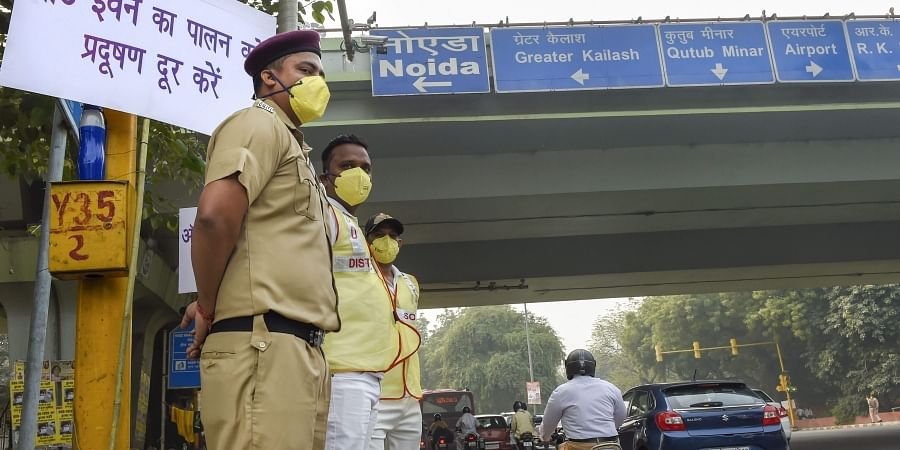 Civil Defence volunteers wearing masks stand near a placard asking people to obey the odd-even rule at ITO in New Delhi.| (File | PTI)
