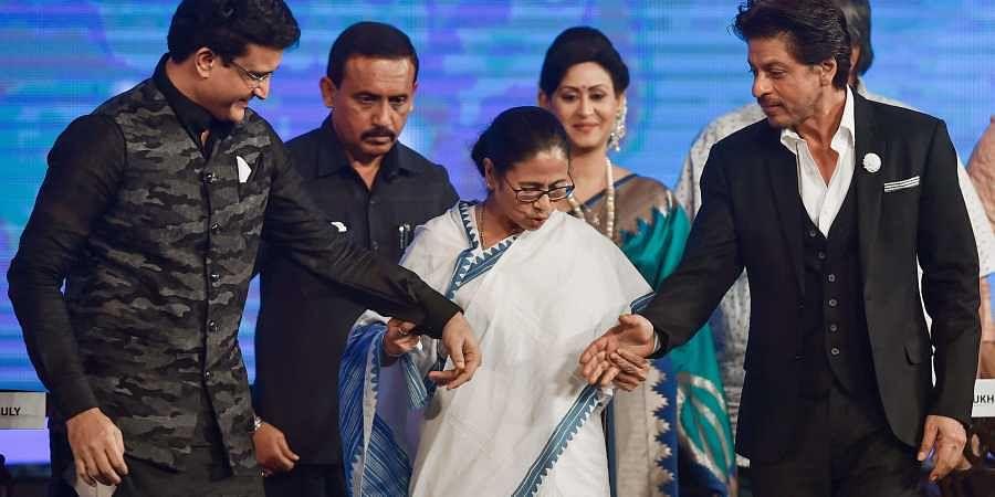West Bengal Chief Minister Mamata Banerjee invites BCCI President Sourav Ganguly and Bollywood actor Shahrukh Khan to shake hands during 25th Kolkata International Film Festival at Netaji Indoor Stadium in Kolkata Friday Nov. 8 2019.   (Photo   PTI)
