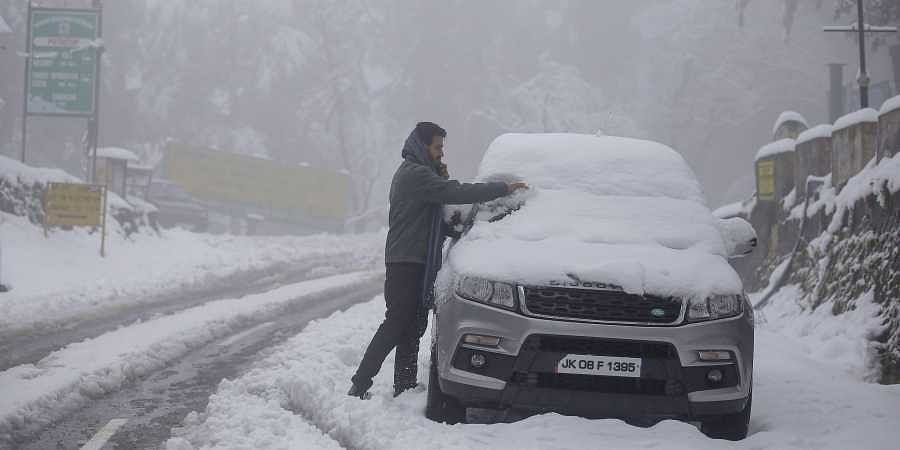 A resident clears snow from his car windshield after fresh snowfall in Patnitop