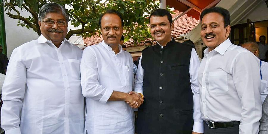 Ex-Chief Minister of Maharashtra Devendra Fadnavis shakes hands with NCp leader Ajit Pawar