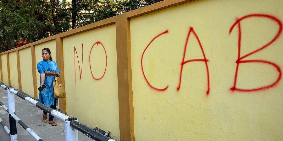 A pedestrain walks past a wall graffiti opposing the Citizenship Amendment Bill CAB in Guwahati Monday Dec. 9 2019. (Photo | PTI)