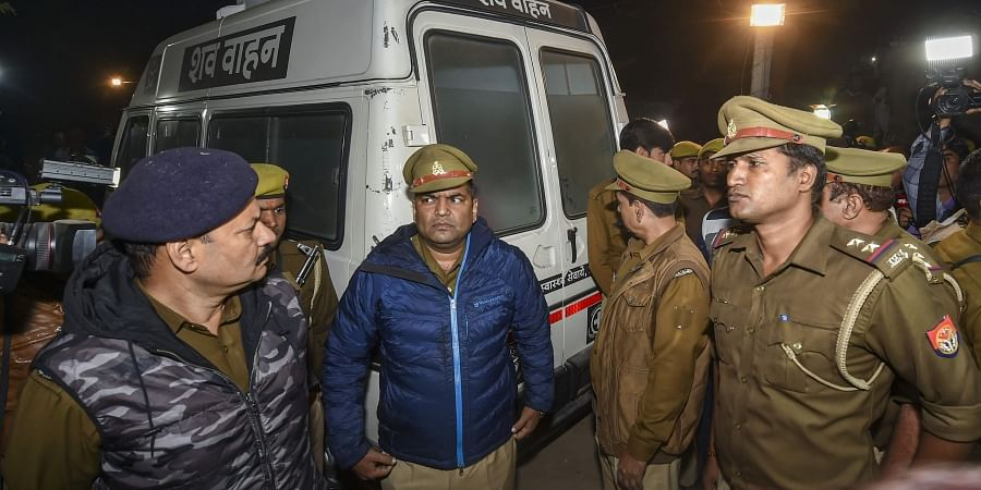Policemen stand near an ambulance carrying the mortal remains of the rape victim who succumbed to severe burns in Delhi hospital arrived at her native village in Unnao district Saturday Dec.7 2019. (Photo | PTI)
