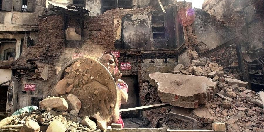 A woman works through the wreckage of a burnt house in Ahmedabad, 07 March 2002