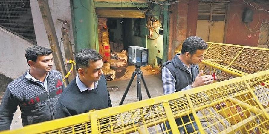 Police officers map the factory site using a 3D mapping device, in Anaj Mandi area near Filmistan, in New Delhi on Tuesday