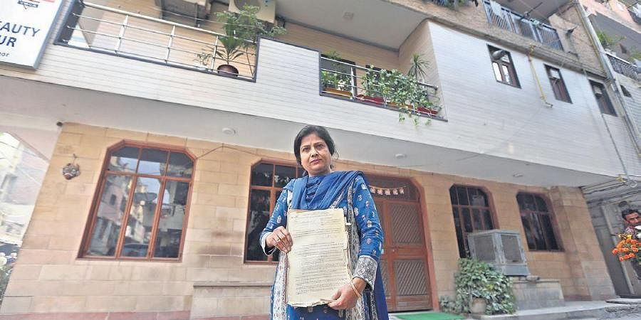 Nafisa Ali, holds a document labelling her as a tenant in the colony