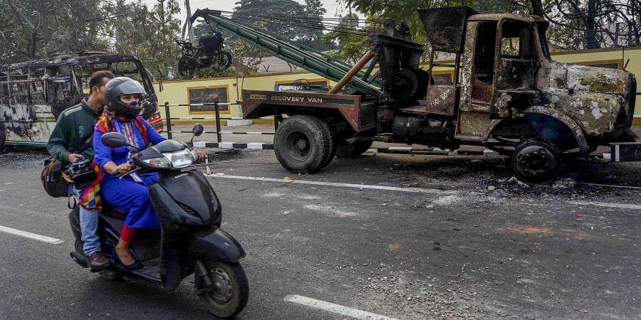 A scooterist rides past charred vehicles which were allegedly set on fire by the protestors during protests against the Citizenship Amendment Bill in Guwahati