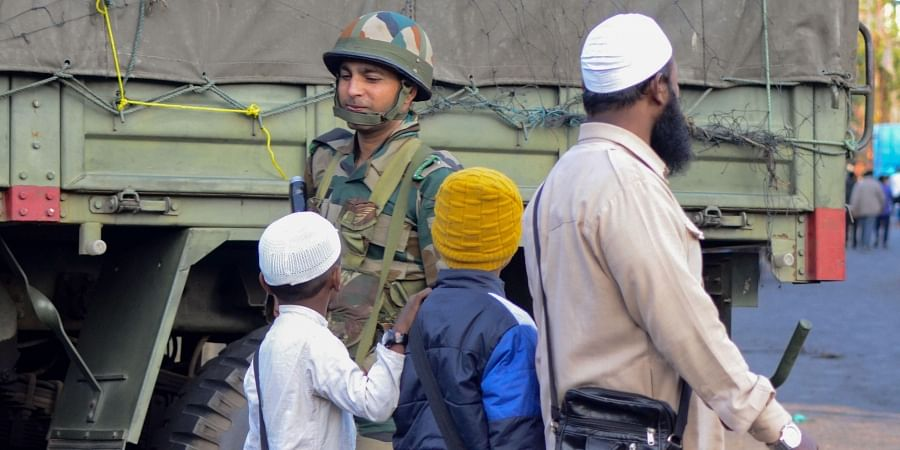 An army jawan guards as a man along with children walks past him during relaxation of curfew in Dibrugarh Friday Dec. 13 2019. (Photo | PTI)