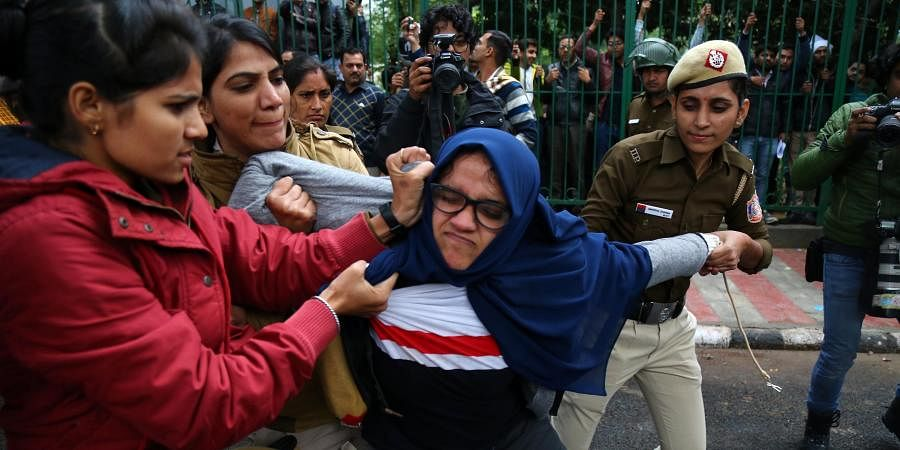 Delhi police officials detain Jamia students during their protest against the passing of Citizenship Amendment Bill, at Jama in New Delhi